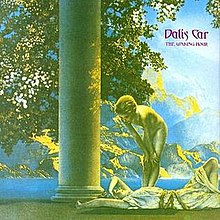 "A predominately green, yellow, and blue saturated Ancient Greek-style image of a girl lying down smiling and another girl standing above her, naked, looking down at her. Next to them is a column. The leaves of a tree are visible directly behind the column. In the background is a large mountain, separated by the sea. ""Dalis Car"", with ""The Waking Hour"" below it in smaller text, are imprinted in fantasy-style purple text in the upper-right corner."