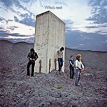 A photograph of The Who walking away from a stone monolith and zipping up their pants, with visible streaks of urine on the structure
