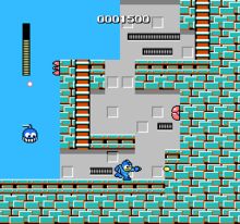 A square video game screenshot that depicts a blue character sprite firing a shot toward a vertical brick wall. Other sprites surround the character and a score are visible at the top of the screenshot.