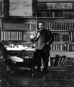 Full length photo of a man dressed in a khaki jacket standing in a book lined study. He has short hair, a moustache and is smoking a pipe.