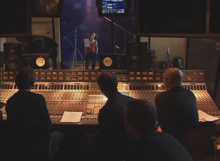 The inside of a music studio. Four men sit in front of a soundboard, while a woman wearing a red shirt stands inside the recording booth.