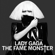 Black-and-white image of Lady Gaga in a blond bob wig with a black collar hiding her mouth.