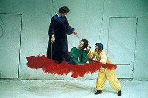 RSC production of A Midsummer Night's Dream (1970) - Amid the blank white set, with its two doors, a red feather on a trapeze represents Titania's bower. Oberon (left) is anointing Titania's eyes with the love potion, while Puck looks on.