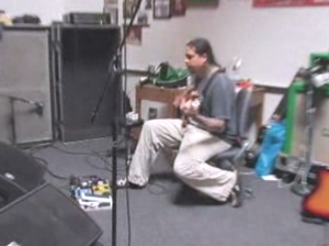 "Eros (Deftones album) - A still from ""Eros In-Studio Video 4,"" one of the five recording-update videos Deftones posted online in 2008 before production was halted. The image depicts bassist Chi Cheng practicing an unknown song from the Eros sessions with his fellow band members."