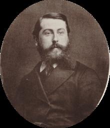 Hombre blanco de mediana edad con cabello corto y oscuro y una barba tupida