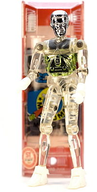 A photo of a vintage Microman M101 (George) 3.75-inch-tall (9.5 cm) action figure with capsule in the background.