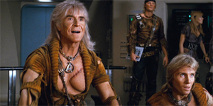 A film still showing Montalbán as Khan on the bridge of a spacecraft, wearing a torn golden shirt. His exposed chest bears a large scar, and his hair is long and grey. In the background, his followers wear similar clothes.