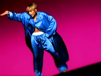 A women wearing a barely-buttoned and wind-blowing bright blue silk pajamas, showing a white boxer inside her pants, with her right hand up and her left hand on her hip, she is backed by a dark pink background.