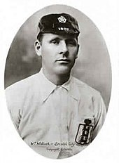 A young man wearing an old-fashioned white football shirt and a dark cap with the date 1907 on it. On his breast pocket is the England football Three Lions logo.