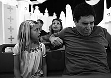 A black-and-white image of a young girl on the left and a middle-aged man sitting on a bench with a patterned background and others doing the same behind them. She is looking at him while he appears to grimace