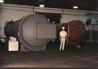 Autoclave (industrial) - Industrial autoclaves used in the aerospace industry. The autoclave on left is gas-fired; the machine on right is electrically heated. At full pressure, the force acting against the door of the grey machine is over one thousand tons. Both machines use rotating lockring doors; the larger one is hydraulically turned, the smaller is pneumatic.