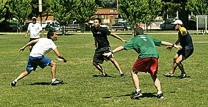 Ultimate (sport) - An offensive player tries to play through a three-man cup defense during an informal game.