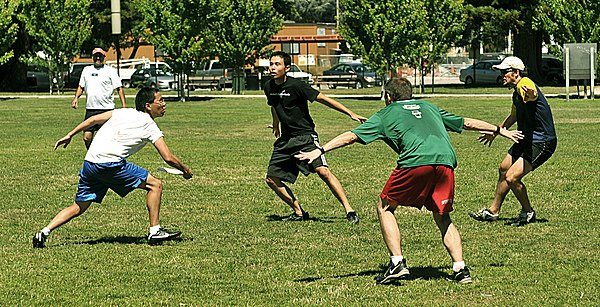 An offensive player tries to play through a three-person cup defense during an informal game. Three-man cup defense in ultimate.jpeg