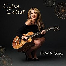 Colbie Caillat crouching, smiling and playing a guitar.