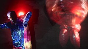 Summertime Clothes - A screenshot from the music video showing one of the clothed figures dancing next to one of the women in giant bubbles.