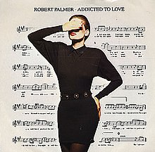 A model with a hand raised covering her eyes, her other hand is on her hip. She is wearing a black dress and dark tights. Her face is heavy with makeup, the white of her face contrasting dramatically with her red lips. The background is a filled by a sheet of music notation.