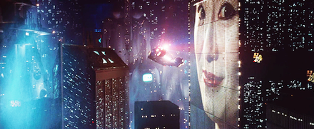 A still frame from the film Blade Runner. A flying car flies between skyscrapers in a futuristic looking city. The buildings are covered with lights and advertising video billboards.