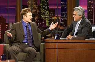 Late-night talk show hosts Conan O'Brien, left, and Jay Leno, right, talk on the set of The Tonight Show years prior in 2004.