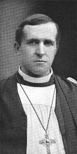 A young-looking dark-haired man faces forward. He is wearing black and white robes and a crucifix.