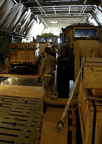 Lockheed C-5 Galaxy - JCB HMEE backhoe loader stowed inside a C-5.  The C-5 loadmasters ensure cargo is secured and balanced before takeoff.