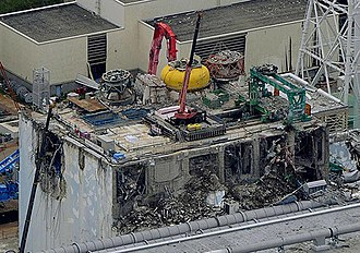 Fukushima Daiichi nuclear disaster - Unit 4 after the hydrogen explosion. The bright yellow object is the lid of the Reactor Containment Vessel. The green object is the crane for the spent fuel pool.