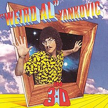 "The cover for ""Weird Al"" Yankovic in 3-D features ""Weird Al"" Yankovic's upper torso protruding out of an askew box with a wooden frame. The title is written in mock three-deminsional font. The sky and a yellow floor are featured in the background."