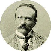 Head and shoulder shot of middle-aged man, moustached, slightly balding