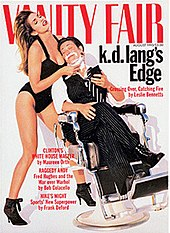 Cover of Vanity Fair magazine from August 1993 showing k.d. lang reclining in a barber chair with eyes closed and holding a compact mirror. She has shaving foam on her chin and is wearing an open-collar white shirt, black and white striped tie, dark color pinstripe vest and cuffed pants, and black lace boots. Supermodel Cindy Crawford is holding a straight razor to lang's chin while lang's head rests on her breast. Crawford is wearing a one-piece black bathing suit and high heel black boots, with head thrown back as her long hair cascades down her back.