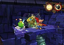 A character in brightly colored attire rings an oversized, gold and blue bell as he stands on a dark, stone platform. Directly in front of him is a green-colored cartoon bomb with a lit fuse. Below the platform is larger bell not completely in view. The upper righthand corner of the image shows two circular icons, the first showing a skull-and-crossbones with rabbit ears and the second showing a movie camera.