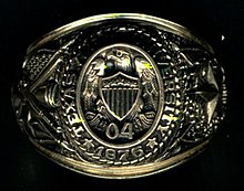 Close-up of gold ring. On the top, the words Texas A&M University 1876 encircle an eagle atop a shield over the numbers 0 and 4. The left side contains a large star and an oak. The right shows a cannon, saber, and rifle with the crossed flags of the United States and Texas.
