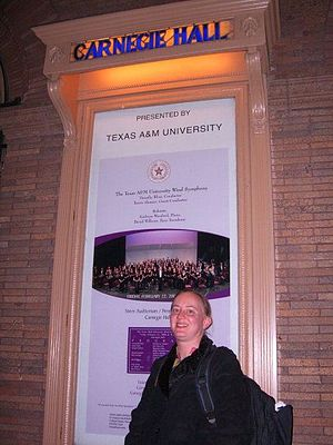 Timothy Rhea - Dr. Kathryn Woodard, piano soloist for the Texas A&M Wind Symphony's concert, poses outside New York City's Carnegie Hall. The poster announces the performance of Dr. Rhea's ensemble, which took place February 22, 2008.