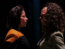 Two women are staring at each other while standing in a dark room. The woman on the right has ridges on her forehead and curly hair, while the one on the left has straighter hair and a uniform with a yellow strip.