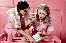 Two young women face forwards, standing over a pink wooden cradle. Both are wearing pink outfits and the background is a pink room. The woman on the left has chin-length dark hair and holds in her right hand a plastic lifelike baby doll. With her left hand she pushes the other woman, who has long, light brown hair and also leans over the doll.