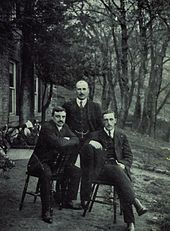 Three men in dark suits, two sitting on chairs and the third stood behind