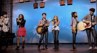 """Send It On (Disney's Friends for Change song) - Left to right: Joe Jonas, Demi Lovato, Nick Jonas, Miley Cyrus, Selena Gomez, and Kevin Jonas singing into their microphones on top of a stage in the """"Send It On"""" music video."""