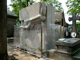 A large rectangular granite tomb. A large, stylised angel leaning forward is carved into the top half of the front. There are a few flowers beside a small plaque at the base, the tomb is surrounded by a protective glass barrier that is covered with graffiti.