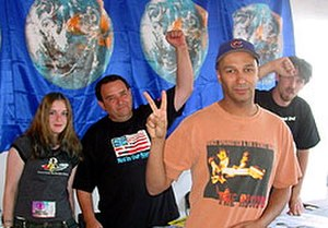 Audioslave - Guitarist Tom Morello (center, wearing hat and giving a peace sign) with Not in Our Name volunteers at an Axis of Justice tent at the July 13, 2003 Lollapalooza festival in Columbus, Ohio