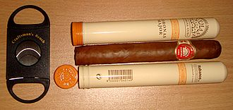 H. Upmann - A double guillotine-style cutter, used for cutting the tip off a cigar, next to two hand-rolled H. Upmann Coronas Major cigars, one inside its storage tube and one outside.