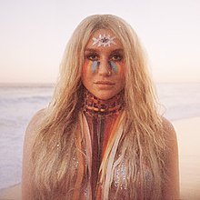 Kesha with various colors painted on her face and neck.