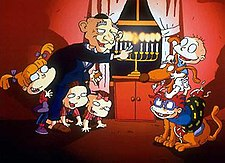 A cartoon of an elderly man lighting a Menorah. He is bald and wearing a Kippah. At his feet are three toddlers; two are on their hands and knees, the other is standing. To their right are two infants sitting on a large brown dog. One infant is bald and wearing a nappy; the other is wearing a t-shirt and shorts.