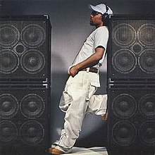 An image of Musiq standing between loudspeakers stacked on top of each other, sporting a white t-shirt, jeans, hat and black headphones.