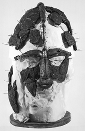 Black and white photograph taken during the second reconstruction, showing the fragments positioned on a head-sized block of plaster and supported with pins