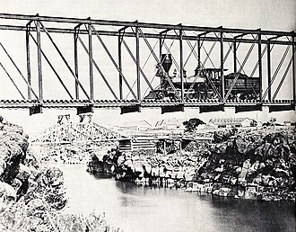 Utah & Northern Bridge circa 1880 with railroad shops in background. View is looking north or upriver.