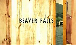 Beaver Falls written in black letters against a wooden door, slightly ajar, showing a lake.