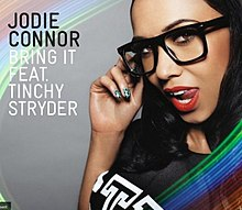 A portrait circled in a rainbow-like colour of a woman seductively posing with her right hand on her large black spectacles. She is wearing bright red lipstick and her tongue is positioned outside the left side of her mouth. To the woman's right in black stands 'JODIE CONNOR' and in white 'BRING IT FEAT. TINCHY STRYDER'.