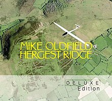 "An aerial photograph of green fields with a white model aircraft flying above. In the centre there is large yellow text with the words ""Mike Oldfield"" and ""Hergest Ridge"". The lower portion of the image has a grey overlay with the words ""Deluxe Edition"" at the lower right."