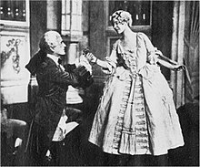 Photo of a scene in upper-class 18th century costume, a young man kneeling and grasping the hand of a young woman, who is standing and leaning towards him