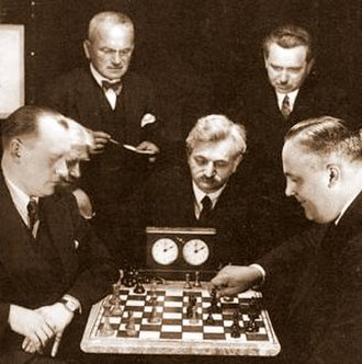 Alexander Alekhine - Alekhine (left) vs. Efim Bogoljubov (right); Emanuel Lasker (sitting, center) and others looking on