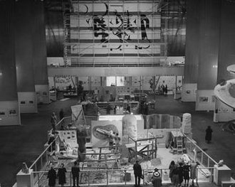 """Art in Action - Art in Action at the Golden Gate International Exposition. """"The Pit"""" with its many artists is at floor level and Herman Volz's mosaic is on the opposite wall. LIFE photographer Peter Stackpole climbed up Diego Rivera's scaffold to take this shot"""