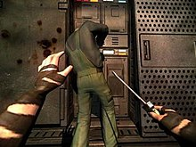 A pair of human arms with brown tape on them holding a screwdriver in the right hand. A man working on a machine, wearing a green jumpsuit and a black shirt, is in front of the arms with blood splatter on the wall to his left.